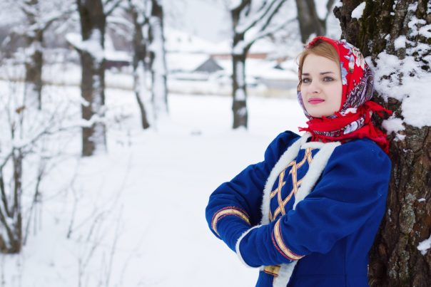 Russian Traditional Clothes. Russian beauty woman in traditional clothes against winter landscape